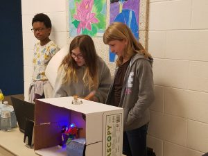 Three young girls standing behind their robotic presentation.