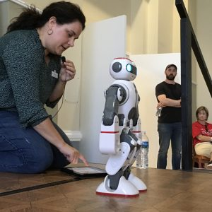 Person kneeling on the stage with hand mic, robot and iPad.