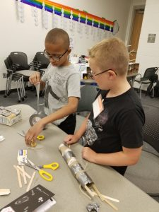 Two boys working together with tape, scissors and other materials.