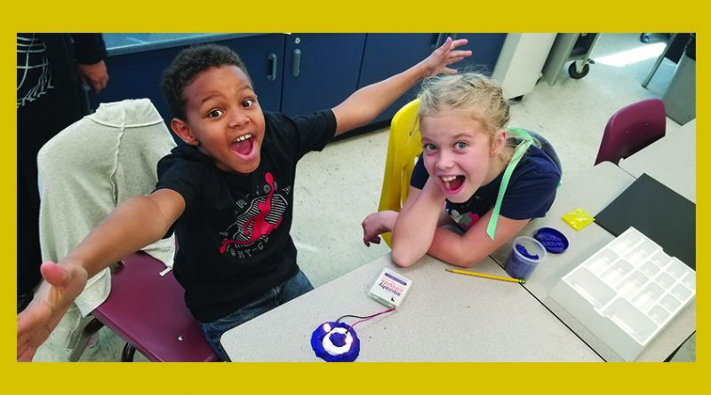 Two students celebrate their Squishy Circuit creation.